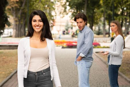 Photo pour Jealousy Concept. Man Being Distracted By Attractive Girl Walking With Jealous Girlfriend Having Date In Park. Selective Focus - image libre de droit