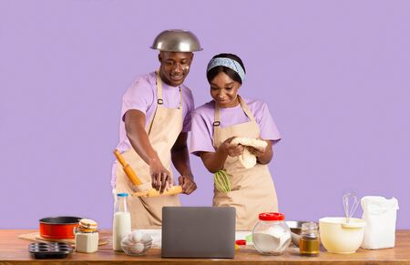 Photo pour African American couple watching online culinary video on laptop while baking, violet background - image libre de droit
