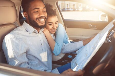 Photo pour Happy Black Couple Hugging In Car Holding Road Map Travelling By Auto In Summer. Road Adventure Concept. Selective Focus - image libre de droit