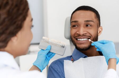 Photo for Female dentist choosing filling shade for smiling black guy, using tooth scale sample, close up - Royalty Free Image