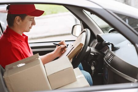 Photo for Modern express delivery service. Courier notes on tablet delivery of package sitting in car - Royalty Free Image