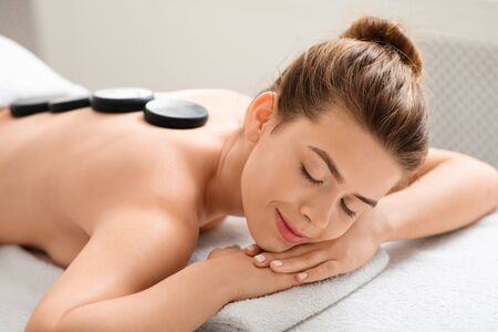 Photo for Attractive woman resting during hot stone massage at spa salon - Royalty Free Image