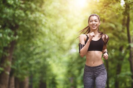 Photo for Healthy Lifestyle. Sporty Asian Girl In Jogging In City Park, Enjoying Morning Workouts, Preparing For Marathon - Royalty Free Image