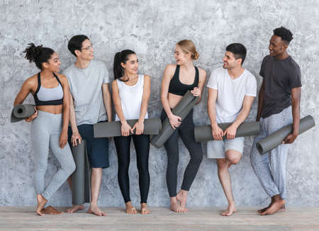 Photo pour Healthy Lifestyle Concept. Group of sporty people with yoga mats resting after class near grey wall in fitness studio - image libre de droit