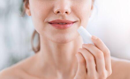 Photo pour Closeup of young woman holding lip balm, home interior - image libre de droit