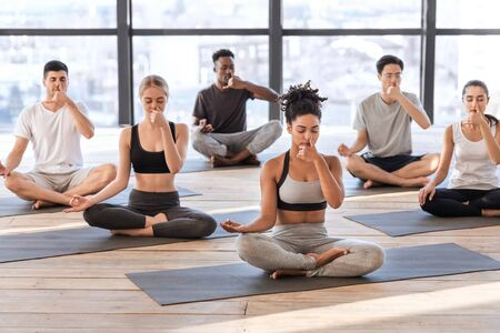 Photo pour Young men and women in yoga studio practicing alternate nostril breathing exercises together, sitting on mats and doing nadi shodhana pranayama asana - image libre de droit