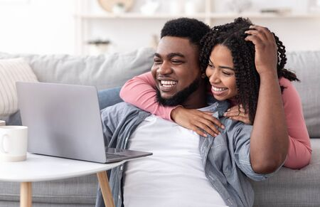 Photo pour Caring Black Woman Supporting Her Boyfriend While He Working On Laptop At Home, Closeup - image libre de droit