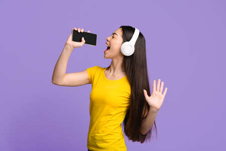 Photo for Candid asian girl singing into smartphone like microphone while listening music via wireless headphones over purple background, copy space - Royalty Free Image