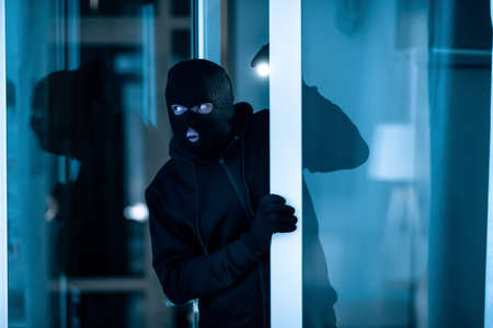 Photo pour Burglary Concept. Watchful thief lurking into residential building through open front door, entering enclosed property - image libre de droit