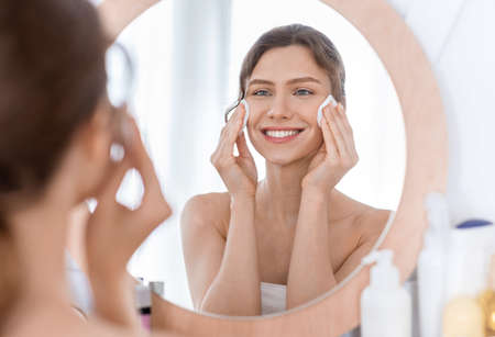Photo pour Skincare. Young cheerful woman looking at mirror and cleaning her face with cotton pads at home - image libre de droit