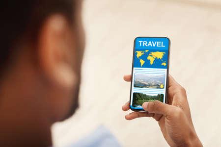 Photo pour Unrecognizable black man reading travel blog on smartphone, researching info for his next journey, over shoulder view with selective focus - image libre de droit