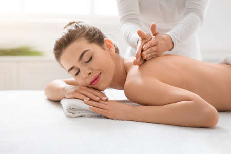 Photo for Peaceful girl getting back massage at cozy spa, side view - Royalty Free Image