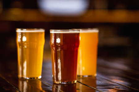 Photo for Beer craft style. Barley, unfiltered, light drink in glasses on wooden table in blurry interior of pub - Royalty Free Image