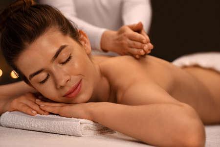 Photo pour Closeup of tranquil young woman enjoying relaxing body massage at spa - image libre de droit
