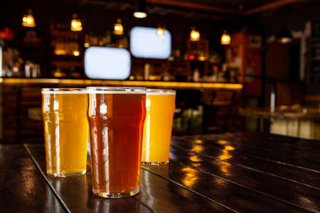 Photo pour Relax with friends. Dark, light, unfiltered beer in big glasses on wooden table in interior of modern pub, close up, free space - image libre de droit