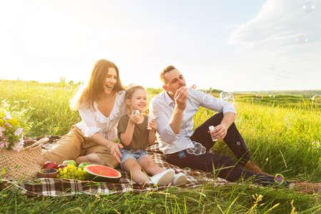 Photo pour Outdoor Activity Concept. Young parents blowing soap bubbles with their child, having family picnic, copy space - image libre de droit