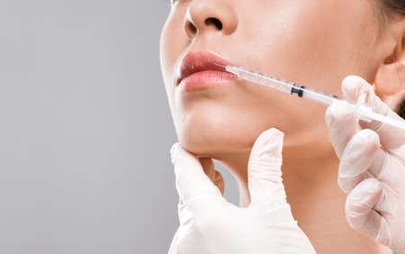 Photo pour Closeup of nurse making lip injection for unrecognizable young woman, copy space - image libre de droit