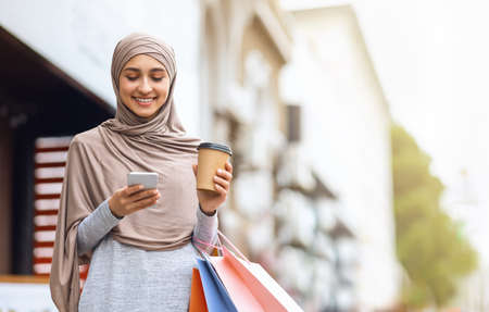 Photo pour Cheerful muslim girl with shopping bags and cup of coffee using smartphone, spending weekend at shopping mall - image libre de droit