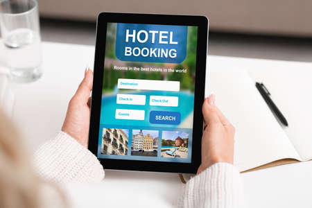 Foto de Businesswoman Booking Hotel Accommodation Online Using Digital Tablet Sitting At Workplace Indoor. Cropped, Collage - Imagen libre de derechos