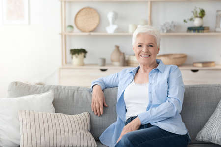 Photo pour Relaxed Elderly Woman Posing On Couch Im Cozy Home Interior, Smiling At Camera, Free Space - image libre de droit