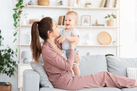 Photo pour Lovely Time Together. Young Mom Bonding With Her Little Baby Son At Home, Playing On Couch In Living Room, Empty Space - image libre de droit