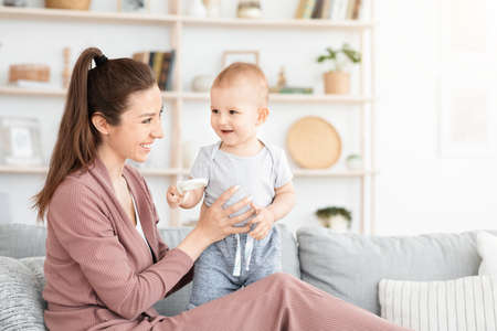 Photo for Portrait Of Mother And Toddler Baby Playing And Laughing Together At Home, Sitting On Couch In Living Room, Copy Space - Royalty Free Image