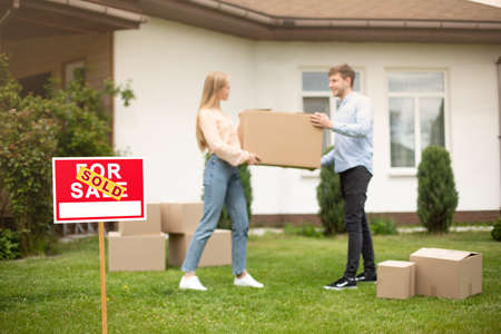 Photo pour Millennial couple with carrying box in front of new home on moving day, focus on SOLD sign. Free space - image libre de droit