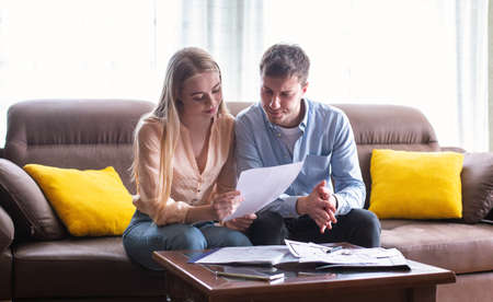 Photo pour Young married couple looking through tenancy agreement in house for sale, panorama - image libre de droit