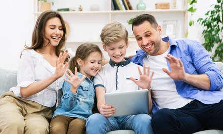 Foto für Family Making Video Call On Digital Tablet Waving Hello Sitting On Sofa At Home. Distant Communication. Selective Focus - Lizenzfreies Bild