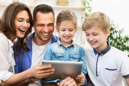 Photo pour Joyful Family Using Digital Tablet Laughing Watching Movie Sitting On Couch, Enjoying Weekend Together At Home. - image libre de droit