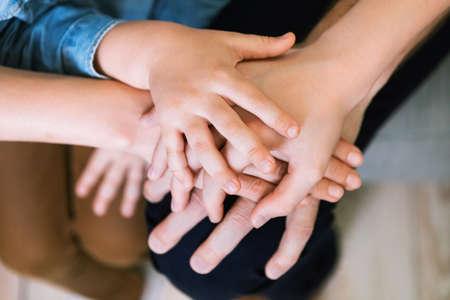 Photo pour Family Bond. Parents And Kids Holding Hands Together Indoors. Cropped, Closeup, Selective Focus - image libre de droit