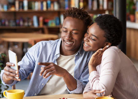 Photo pour Happy black couple browsing internet on smartphone during their date at coffee shop - image libre de droit