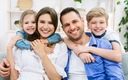 Photo pour Smiling Young Family With Children Posing Sitting On Couch At Home, Looking At Camera. Happy Parents And Kids - image libre de droit