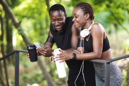 Photo pour Sporty African Couple Resting After Working Out Outdoors, Using Smartphone And Drinking Water, Enjoying Training Together, Closeup - image libre de droit