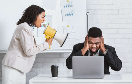 Photo pour Angry African American lady boss with loudspeaker screaming at frightened male employee in office, panorama - image libre de droit