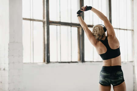 Photo pour Stretching and motivation. Muscular adult woman in sportswear with fitness tracker, gloves and headphones doing exercises in gym or at home - image libre de droit