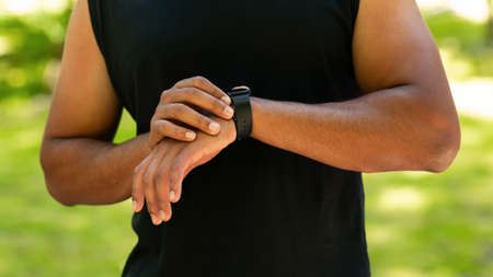 Photo pour Cropped view of black guy checking his smartwatch or fitness tracker while working out outdoors, panorama - image libre de droit