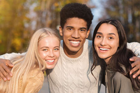 Photo for Portrait of three multiethnic friends guy and girls smiling over park background, close up - Royalty Free Image