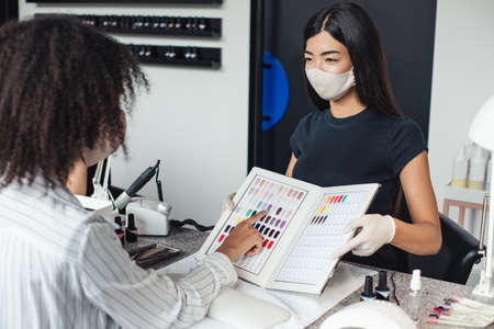 Beauty day and coronavirus. Asian girl in protective mask looks at african american client, chooses color for manicure in nail studio interior