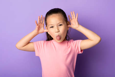 Photo pour Portrait of cute asian kid sticking out her tongue and goofing at studio, isolated on pastel purple background - image libre de droit