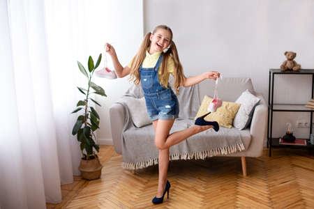 Photo pour Full length portrait of excited teenager posing in blue high heels shoes, holding sneakers by laces - image libre de droit
