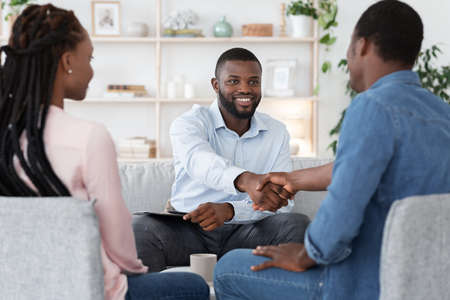Photo pour Marriage Counseling. Thankful Black Couple And Marital Therapist Shaking Hands After Successful Meeting In Office, Selective Focus - image libre de droit