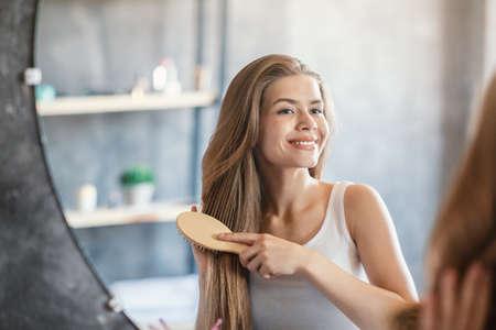Foto de Portrait of happy blonde lady brushing her long hair near looking glass at bathroom - Imagen libre de derechos