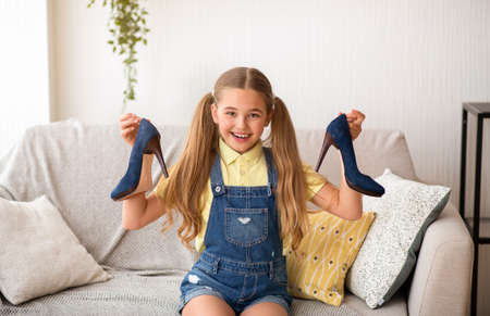 Photo for Portrait of a joyful little girl holding pair of high heels shoes, sitting on couch in living room - Royalty Free Image