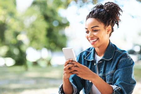 Photo pour Happy Black Girl Using Mobile Phone App Browsing Internet Sitting In Park Outside. Empty Space For Text - image libre de droit