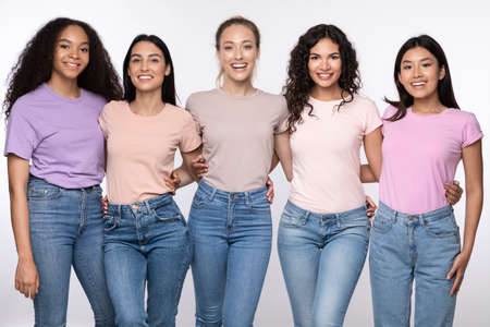 Photo pour Group Of Five Cheerful Multicultural Ladies Embracing Posing Standing Over White Background, Smiling To Camera. Female Friendship, Diversity And Unity Concept. Studio Shot - image libre de droit
