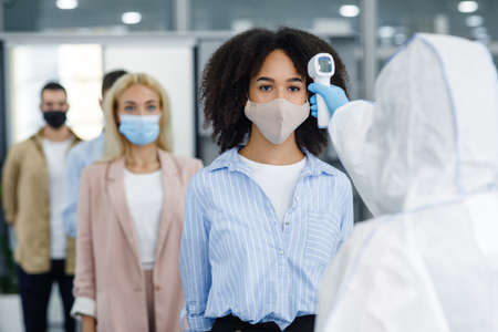 Foto de New normal during outbreak of covid-19. Checking temperature of multiracial workers in protective masks with infrared thermometer in coworking office - Imagen libre de derechos