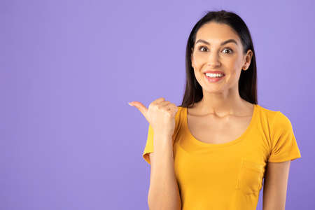 Photo pour Cool Offer Concept. Portrait Of Excited Young Surprised Woman Pointing Finger At Copy Space Isolated Over Purple Studio Background. Crazy Emotional Female Model Indicating Free Space, Banner - image libre de droit
