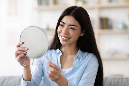 Photo pour Beautiful Asian Woman Holding Magnifying Mirror At Home, Looking At Her Reflection, Enjoying Look Of Her Perfect Face Skin And Smiling, Happy With Results After Beauty Treatments, Free Space - image libre de droit