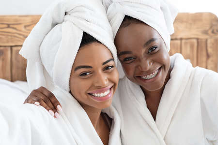 Photo pour Two pretty cheerful african american young women having ladies day at home, wearing bathrobes, sitting on bed. Black female friends embracing and smiling, bedroom interior, closeup portrait - image libre de droit